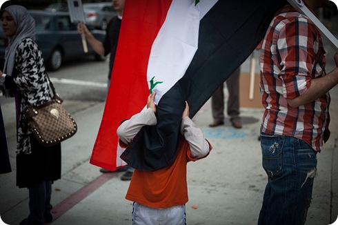 A boy hides behind the Syrian flag held by an actvist at a rally in support of Arab anti-goverment revolutions on Saturday afternoon outside the Federal Building on Wilshire Blvd.
